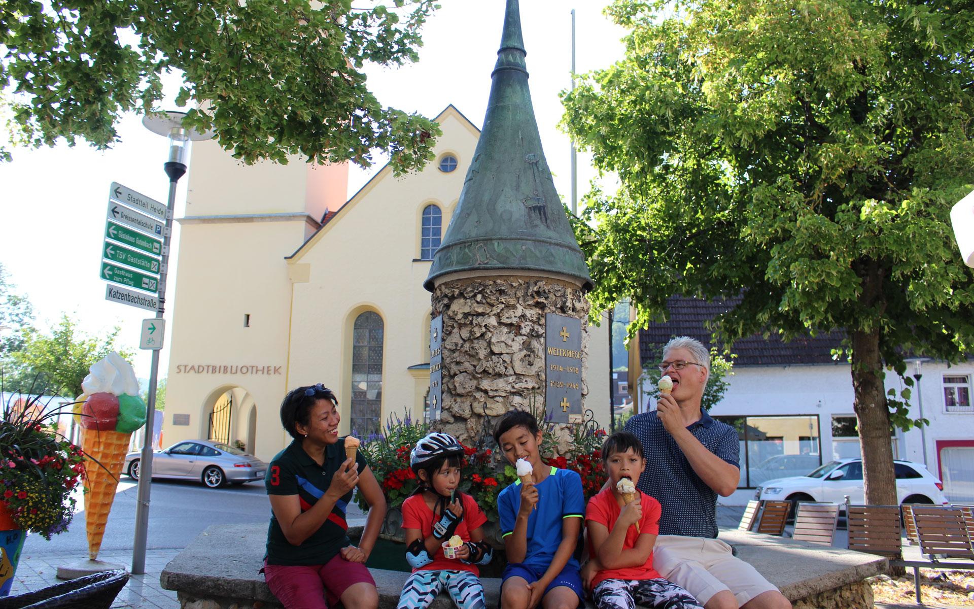 Familie sitzt am Brunnen und isst Eis
