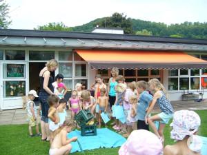 Kinder stapeln im Sommer beim Ferienprogramm leere Getränkekisten