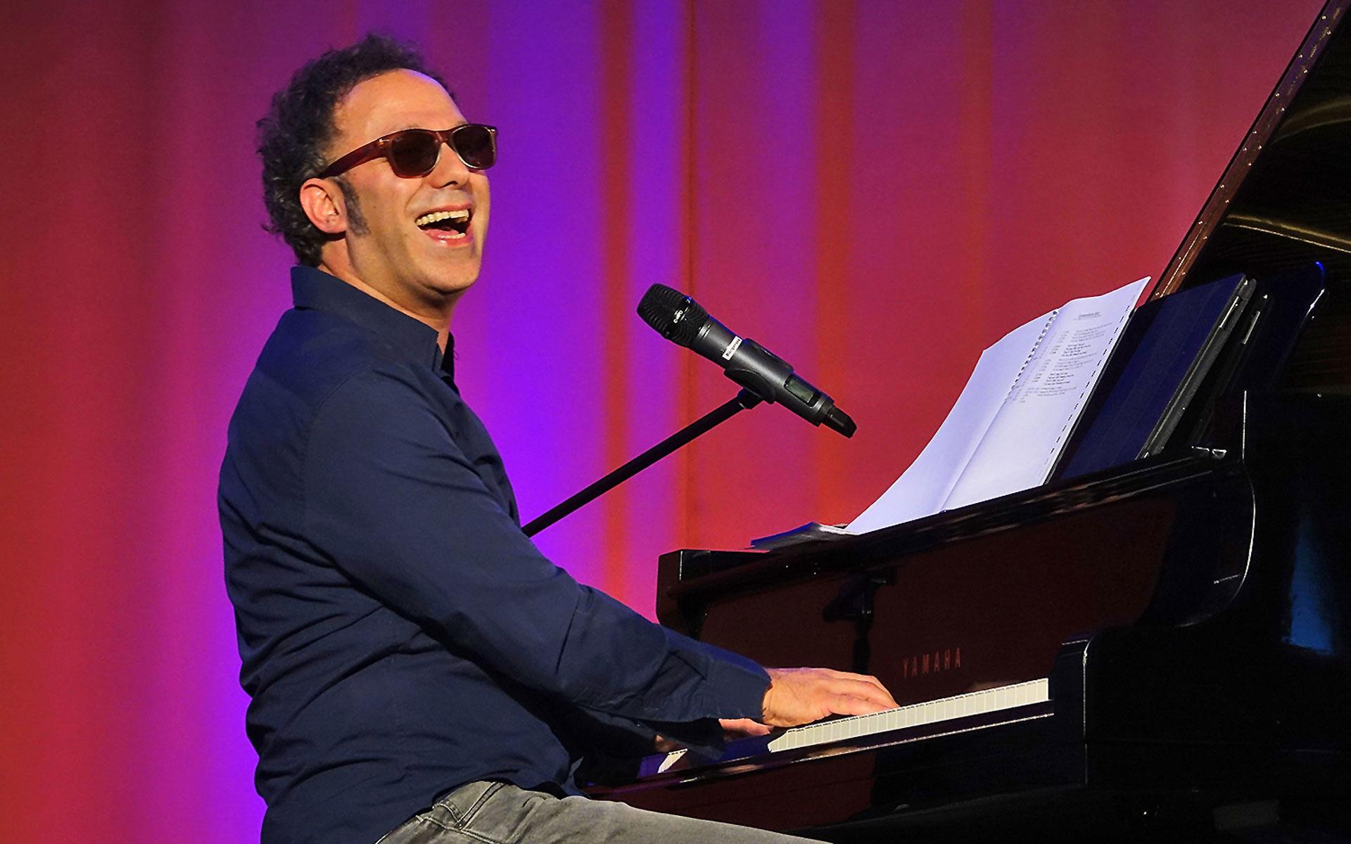 Murat Parlak - Musiker mit Sonnenbrille sitzt am Flügel und singt