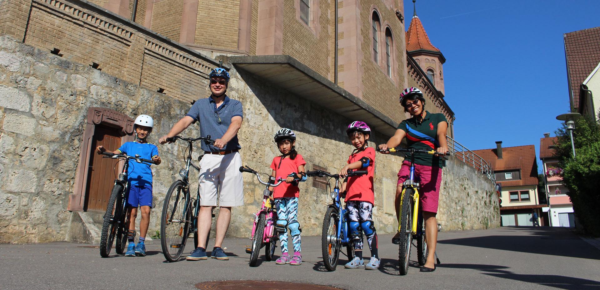 Eine Familie mit drei Kindern steht mit ihren Fahrrädern im Sommer vor der katholischen Kirche