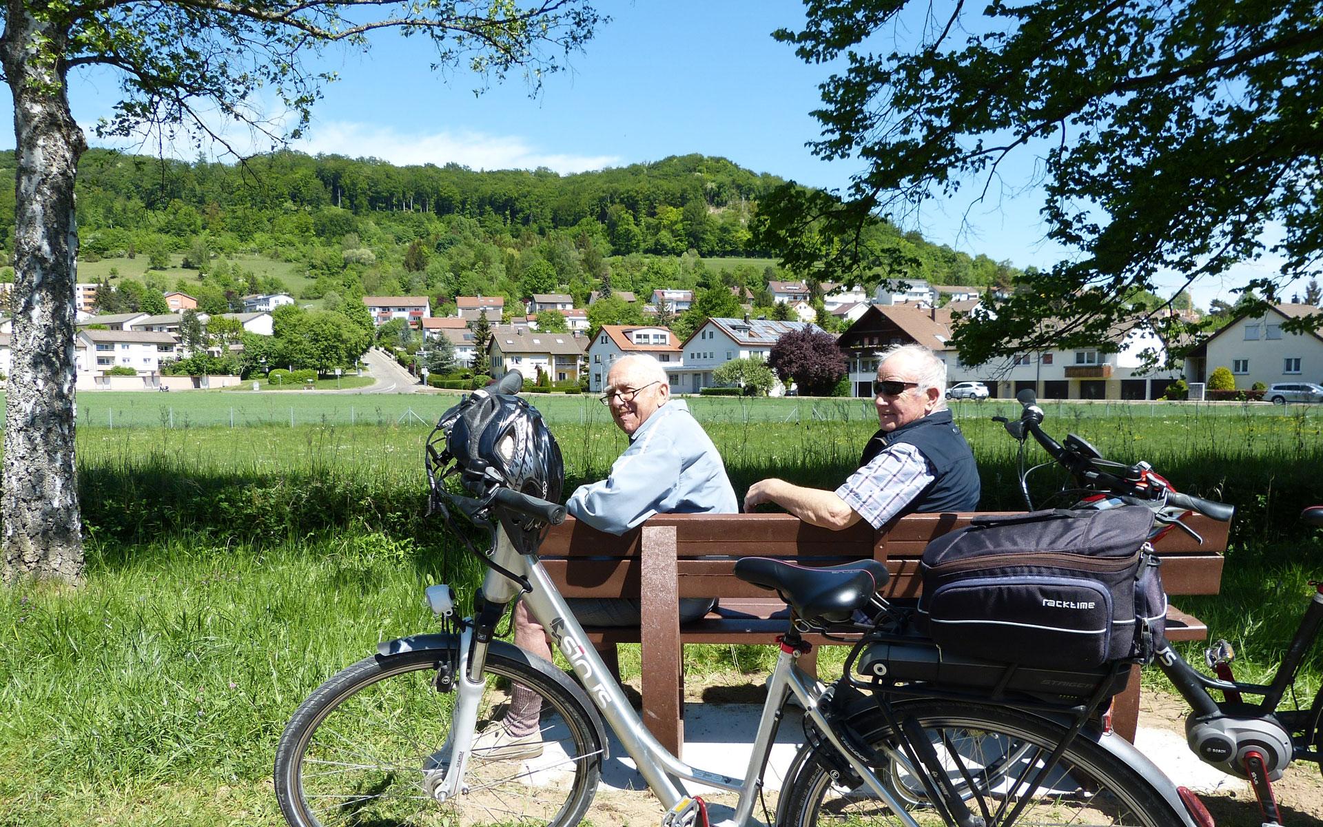 Zwei Radfahrer im Seniorenalter sitzen auf einer Bank und schauen in die Kamera. Im Vordergrund steht ein Fahrrad.