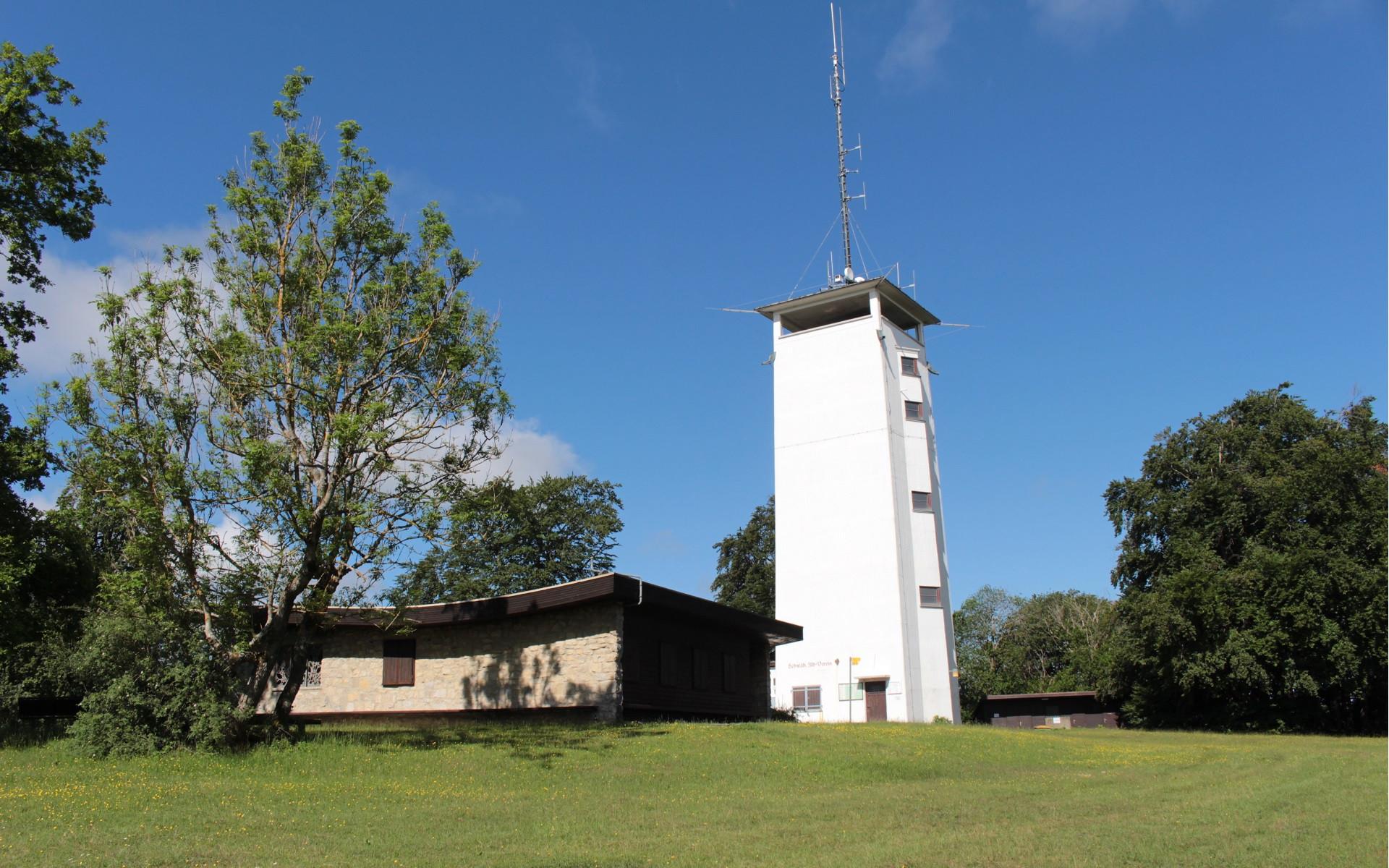 Auf dem Volkmarsberg steht ein weißer Turm mit Schutzhütte vor blauem Hintergrund.